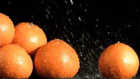 Tasty oranges in super slow motion receiving water stock video footage