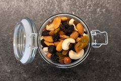 Tasty organic different nuts in glass jar on dark table.  Healthy food and snack. stock images