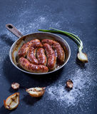 Tasty oven-baked sausages in a frying pan on a dark background. Stock Photos