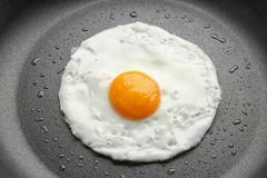 Tasty over easy fried egg in pan. Closeup stock photos