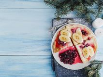 Tasty pancakes with a banana, maple syrup and cranberries. On a background of candles and a Christmas tree branch stock photography