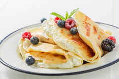 Tasty pancakes with cottage cheese and berries and powder sugar. Closeup of tasty pancakes with cottage cheese and berries and powder sugar Royalty Free Stock Images