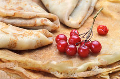 Tasty pancakes with fresh berries. Fresh golden pancakes with berries viburnum. Homemade pancakes. Russian pancakes close-up. Pancake Tuesday Stock Photography