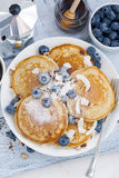 Tasty pancakes with fresh blueberries and honey for breakfast. Top view Stock Photos