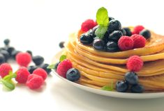 Tasty pancakes with fruits. Pancake with fresh raspberry, blueberry and honey with fresh mint leafs Stock Photography