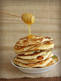 Tasty pancakes with honey and wooden dipper Stock Photos