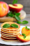 Tasty pancakes with syrup and grilled nectarines on a white plate. Home sweet pancake recipe. Summer breakfast or brunch Stock Photography