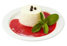 Tasty panna cotta with strawberry jam and fresh mint on a white plate. stock images