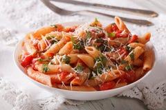 Tasty pasta arrabbiata with parmesan closeup on the table. horiz Royalty Free Stock Images