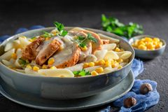 Tasty pasta with bechamel sauce, chicken and corn. On black table royalty free stock images