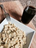 Tasty pasta and coke. Delicious and fresh pasta on wooden board near black coke in glass Royalty Free Stock Photography
