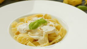 Tasty pasta with mushrooms, fresh basil and cream sauce stock footage