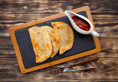 Tasty pasties  filled with meat and vegetables on board with red Stock Photo