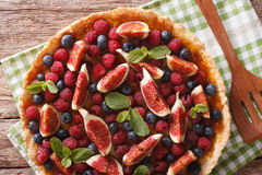 Tasty pastry: tart with fresh figs, raspberries and blueberries Stock Photos