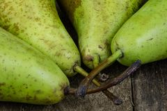 Tasty pears in a jute sack lying on a wooden kitchen table. Frui Stock Photos