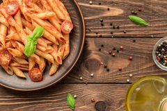 Tasty penne with tomato sauce, fresh basil and tomatoes Stock Image