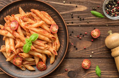 Tasty penne with tomato sauce, fresh basil and tomatoes Stock Photography