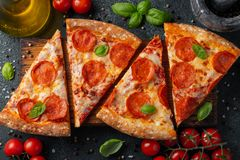 Tasty pepperoni pizza and cooking ingredients tomatoes basil on black concrete background. Top view of hot pepperoni pizza. Flat royalty free stock photo