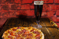 Tasty pepperoni pizza on wooden table near a glass of dark beer Royalty Free Stock Photography
