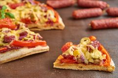 Tasty piece of pizza with salami, tomatoes, bell pepper, onion, green olives, corn, cheese and spices Stock Images