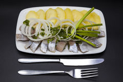 Tasty pieces of Icelandic herring with boiled potatoes and onions on the plate. Stock Photos