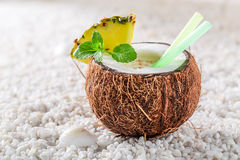Tasty pinacolada in coconut with pineapple and mint leaves Stock Photography