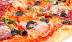 Tasty pizza. Colorful tasty pizza with olives, pepperoni, ham and pepper, close-up shot Royalty Free Stock Image