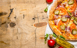 Tasty pizza with bacon and tomatoes. On wooden table. Royalty Free Stock Photography