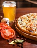 Tasty pizza with beer on wooden table stock photo