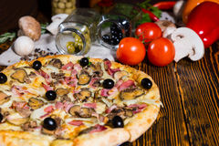 Tasty pizza with ham and black olives on wooden table and other Stock Photos