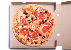 Tasty pizza with ham and tomatoes in box Royalty Free Stock Image