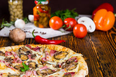 Tasty pizza with pickles on wooden table, tomatoes and other veg Royalty Free Stock Image