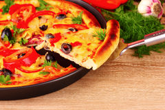 Tasty pizza on the plate and vegetables on wooden Royalty Free Stock Images
