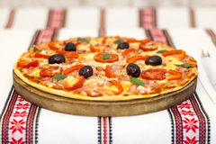 Tasty pizza with vegetables, basil, olives, tomatoes, green pepper on cutting board, table cloth traditional colorful.  Royalty Free Stock Photo
