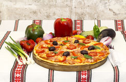Tasty pizza with vegetables, basil, olives, tomatoes, green pepper on cutting board, table cloth traditional colorful.  Stock Photography