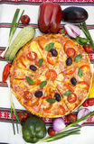 Tasty pizza with vegetables, basil, olives, tomatoes, green pepper on cutting board, table cloth traditional colorful.  Stock Photo