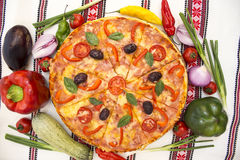 Tasty pizza with vegetables, basil, olives, tomatoes, green pepper on cutting board, table cloth traditional colorful.  Stock Photos