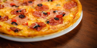 Tasty pizza on a white plate presented on a wooden table Stock Images