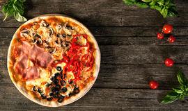 Tasty pizza on a wooden background. Tasty pizza on a wooden background four seasons Royalty Free Stock Photography