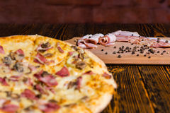 Tasty pizza on wooden table, focus on cutting board with bacon a Stock Photo