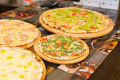 Tasty pizzas with variety of toppings and cheese on wooden trays Stock Image