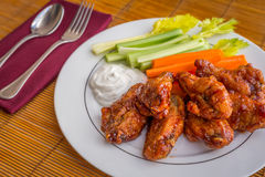 Tasty plate of glazed chicken wings with carrots, celery and dipping sauce. Royalty Free Stock Images