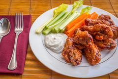Tasty plate of glazed chicken wings with carrots, celery and dipping sauce. Royalty Free Stock Photo