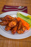 Tasty plate of glazed chicken wings with carrots, celery and dipping sauce. Stock Photos
