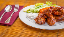 Tasty plate of glazed chicken wings with carrots, celery and dipping sauce. Stock Photography