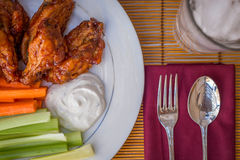 Tasty plate of glazed chicken wings with carrots, celery and dipping sauce. Stock Images
