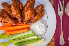 Tasty plate of glazed chicken wings with carrots, celery and dipping sauce. Royalty Free Stock Image
