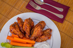 Tasty plate of glazed chicken wings with carrots, celery and dipping sauce. Stock Photo