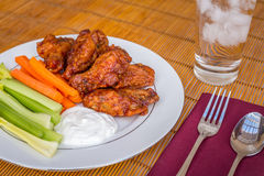 Tasty plate of glazed chicken wings with carrots, celery and dipping sauce. Royalty Free Stock Photography