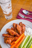 Tasty plate of glazed chicken wings with carrots, celery and dipping sauce. Royalty Free Stock Photos